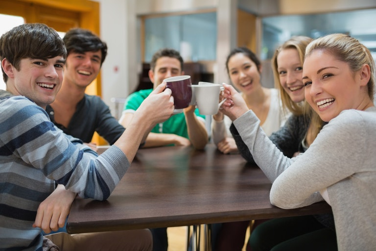 Students clinking cups while smiling