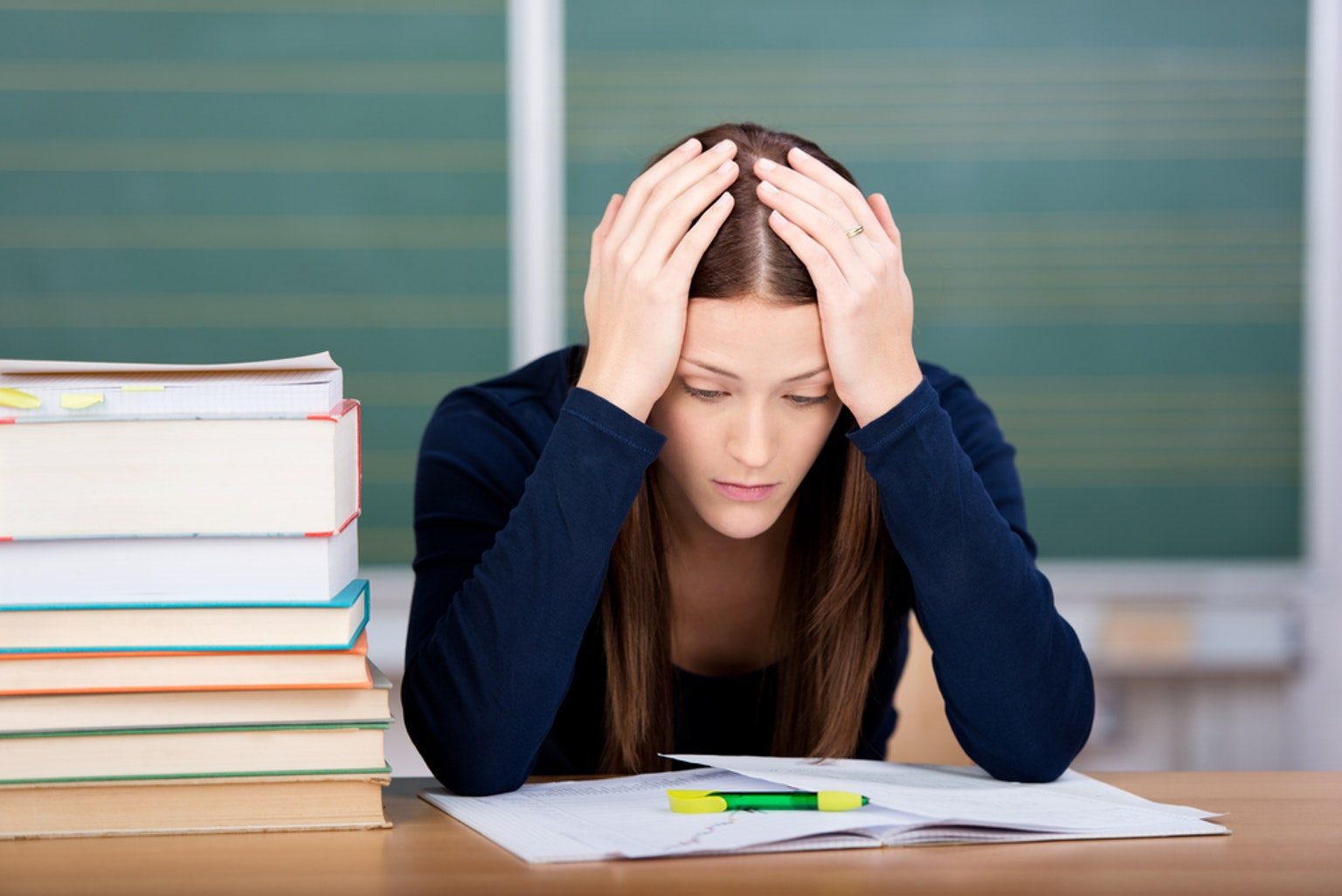 Student with hands on head while looking at papers