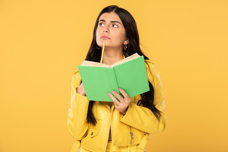 Female holding book while holding pencil against chin